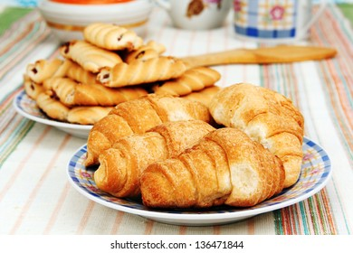 four croissants on a plate in the foreground and a plate of cookies in the background.