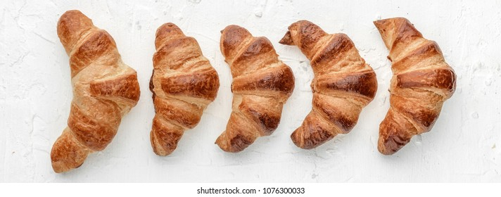 four croissants on a white background
