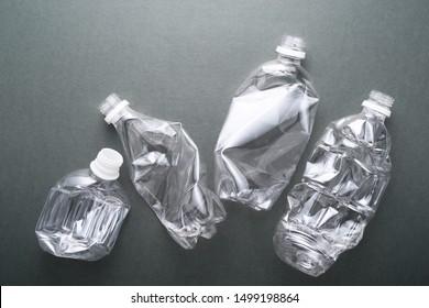Four crush bottles on dark background. Waste of plastic bottles.