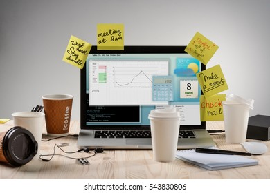 Four cups of coffee at the workplace for an employee with a lot of tasks and a pressing deadline. Yellow sticky notes glued to the monitor of the modern laptop. Work avalanche to the end of the month.