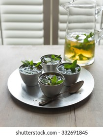 Four cups and a glass pitcher filled with mint julep.