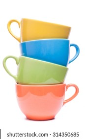 Four cups stacked. Colored mugs. Colorful image with tableware. Isolated yellow, blue, green and pink utensil. Family dishes with different colors.