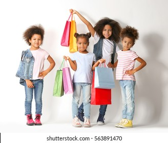 Four cute African girls with shopping bags on white background