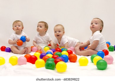 Four cute funny babies sitting on the white blanket and playing colorful balls. Infant party