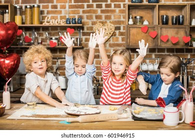 Four cute little children cooking biscuits and showing hands in flour