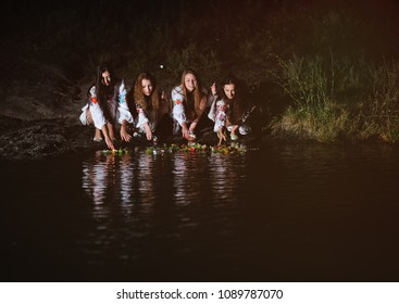 four cute young girls in white shirts with floral ornaments let wreaths of flowers on the river. The celebration of the pagan Slavic holiday of Ivan Kupala Day or Midsummer