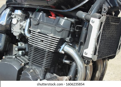 Four cylinder four carburettor four stroke motor bike inline engine with cooling fins and cooling radiator close up