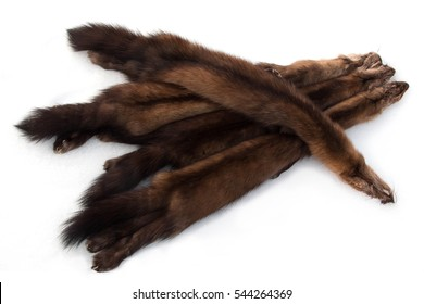 Four dark Russian sable fur pelts laid out on snow, high-contrast background