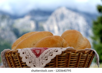 Four delicious traditional Italian roll bread in Willow Bread Basket on the table. The background image is blurred high rock formations and the peaks of the Brenta Dolomites, Trentino, Italy.