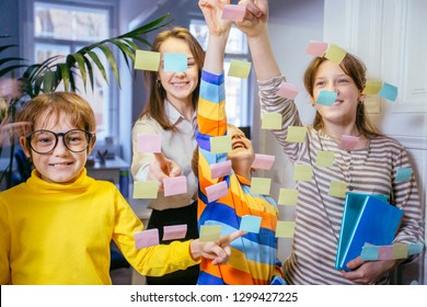 Four different ages children laughing while working together during brainstorming and standing behind glass wall with sticky colorful papers. Cheerful pupils learning words from stickers.