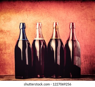 Four different bottles with young wine on red background