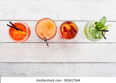 Four different Cocktails with ice ,soda, orange, mint, lime on wooden background top view.