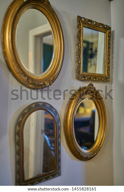 Four different gilt framed mirrors hanging on a wall as decorative elements