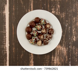 Four different Healthy Homemade chocolate truffles with dates, apricots, hazelnuts and raisins served on white plate on wooden background (photo from above)