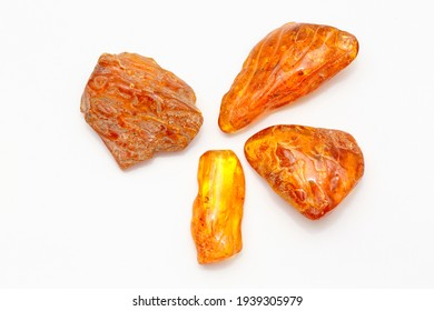 Four different transparent polished yellow amber pieces on a white background. Sun stone. Natural mineral material for jewelry. Amber texture. Copal. Multicolored yellow background. Ancient  resin