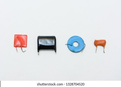 Four different type and color capacitors. Ceramic, film and metal type capacitors. Square tiny red, black rectangular, blue round, orange film capacitor.   On white background