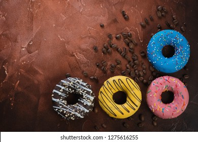 Four different types of donuts with coffee beans on a fire-warm rusty metal background, flatlay with copyspace