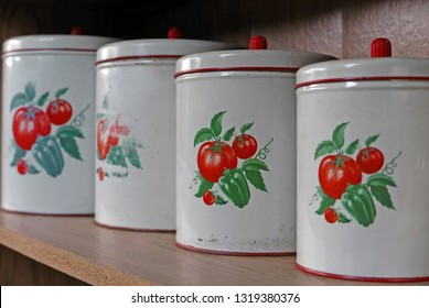 Four different-sized vintage lidded containers with a tomato motif