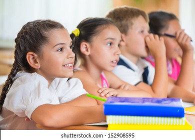Four diligent pupils sitting in row and studying at classroom