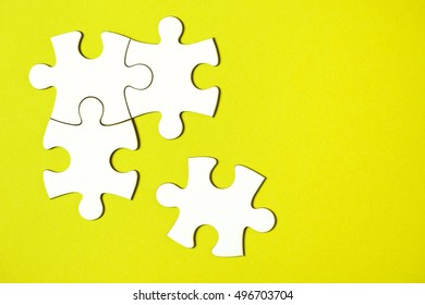 Four disconnected jigsaw puzzle pieces on yellow background. The concept of finding the right solutions in teamwork.
