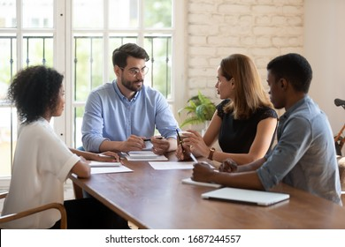 Four diverse business partners negotiating in boardroom. Businesspeople talking solving issues together, workgroup working on common project, share solutions, meeting lead by caucasian female leader
