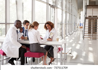 Four doctors looking at laptop in a modern hospital lobby