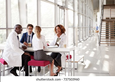 Four doctors talking at a table in a modern hospital lobby