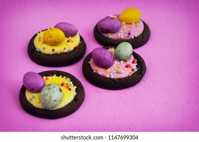 Four Easter Biscuits Staggered on a Pastel Pink Background.