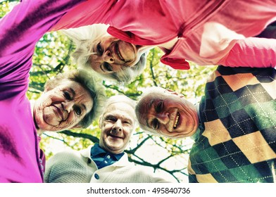 Four elder people looking down to camera relaxing happy outdoor.