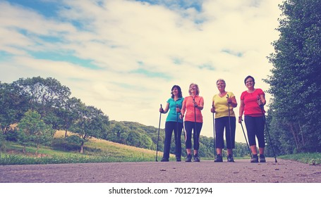 four elderly women to keep fit and healthy with nordic Walking in autumn