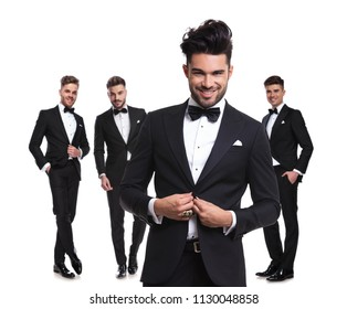 four elegant man standing on white background with hands in pockets, with leader buttoning his tux in front