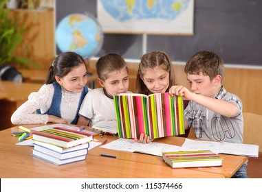 Four elementary aged pupils reading book in classroom