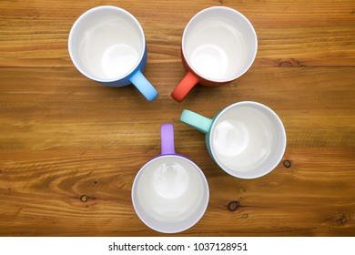 four empty ceramic coffee mugs, in various color, on natual brown wooden table top, top view, directly from above, copy space