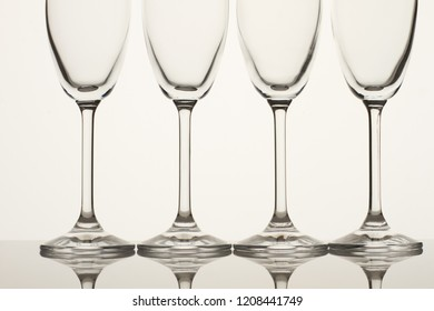 Four empty champagne glasses close up. White background.