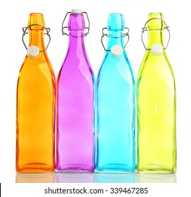 Four empty colourful bottles, isolated on white