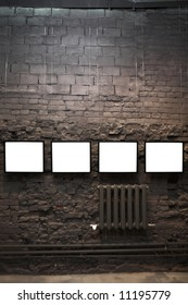 Four empty frames on brick wall in museum