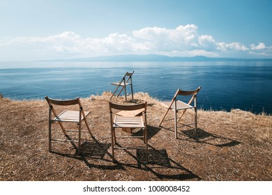 Four empty stools stand on the edge of the rocks against the background of the blue sky and the sea in Greece