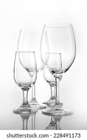 Four empty wine glasses overlapped isolated white.