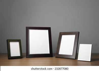 Four empty(blank) wood photo frames(walnut, steel) on the wood table(desk) at the studio.