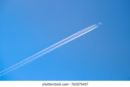 Four engined airplane flying through blue sky with long vapor trails