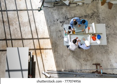 Four engineers in team making a discussion at construction site with several color helmets, taken from  bird eye views or top view
