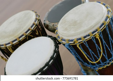 Four ethno drums indoors. Wood background, close-up view. Darbuka and djembe, objects.