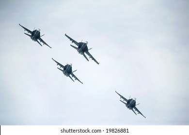 Four F/A-18 Hornet conduct a maneuver in the air during a show
