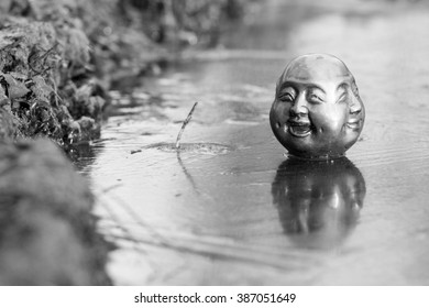 a four face buddha sitting on iced pond. Face for happiness and content are shown.