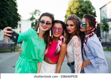 Four fashionable and beautiful best girlfriends in glasses, posing do general self for social networks, lifestyle, spend time fun. Women in sunglasses after shopping and beauty salon.