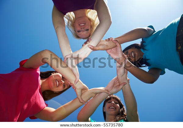 Four female friends holding each other on the wrists