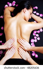 Four female hands giving a lower back massage of a beautiful woman