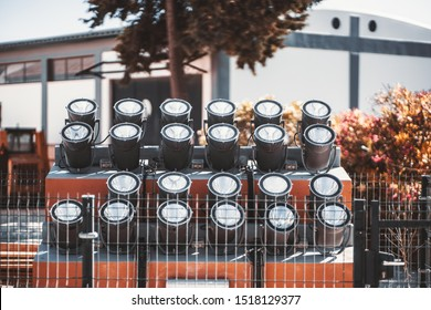 Four fenced rows of powerful spotlights directed upwards on the ground as a part of landscape lighting equipment installation outdoors to illuminate big objects at night