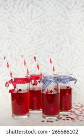 Four festive glasses with red juice, decorative stars and striped straws