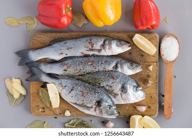 Four fish. Two fresh dorado fish and two sea bass carcasses for grilling with spices (salt, pepper, onion, lemon, kettle, bay leaf) on a wooden tray